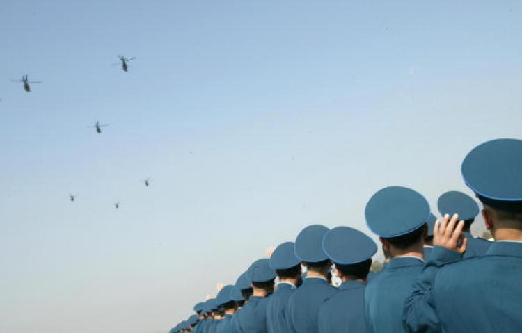 Chinese People's Liberation Army air force officers wave goodbye to helicopters leaving Hong Kong to go back to China during the city's annual rotation of military personnel. (Alex Hofford/AFP/Getty Images)