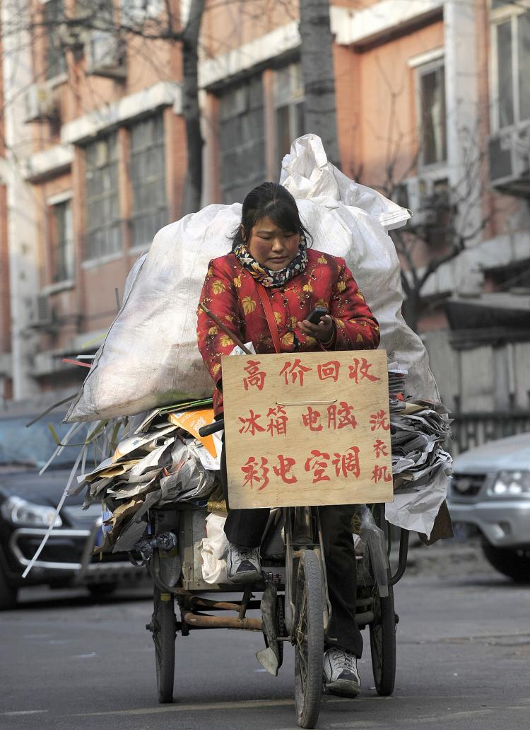 A woman rides a tricyle loaded with recyclable materials in Beijing. (Liu Jin/AFP/Getty Images)