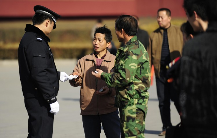 A policeman checks a visitor's ID card at Tiananmen Gate in Beijing on March 1, 2009.      (Peter Parks/AFP/Getty Images)