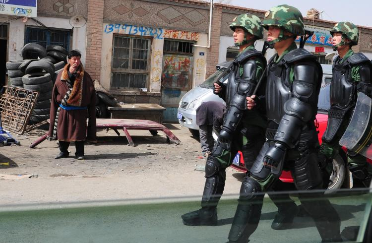 A Tibetan man (L) in traditional clothing watches as Chinese paramilitary troops in riot gear march along the streets of Guomaying,on the Tibetan plateau.(Frederic J. Brown/AFP/Getty Images)