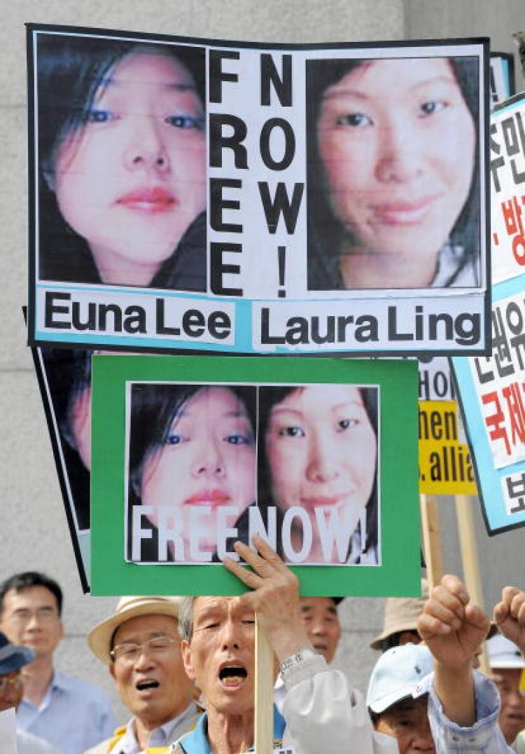 A South Korean conservative activist holds pictures of U.S. journalists Euna Lee (L) and Laura Ling (R) during a rally denouncing North Korea's detention of the journalists in Seoul.  (Jung Yeon-je/AFP/Getty Images)