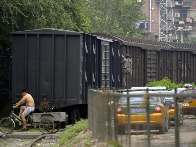 A man rides a tricycle over the rails next to a cargo train in Beijing