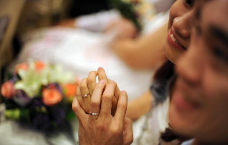 A newly-wed couple gesture after exchanging wedding rings during a mass wedding ceremony at Thean Hou temple in Kuala Lumpur on September 9, 2009. Yet not all Chinese couples can be so open about their relationship. (Saeed Khan/AFP/Getty Images)