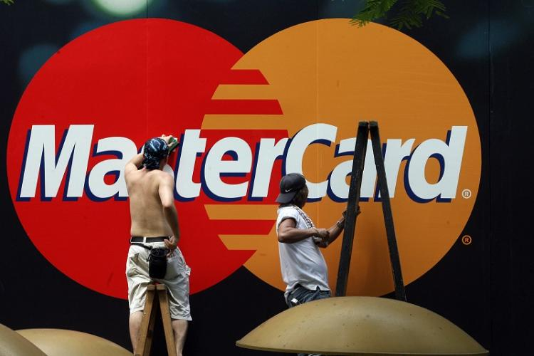 Workers clean a Mastercard advertisement in China. Credit card debt overdue by six month or more has risen sharply since last year. (Mike Clarke/AFP/Getty Images)