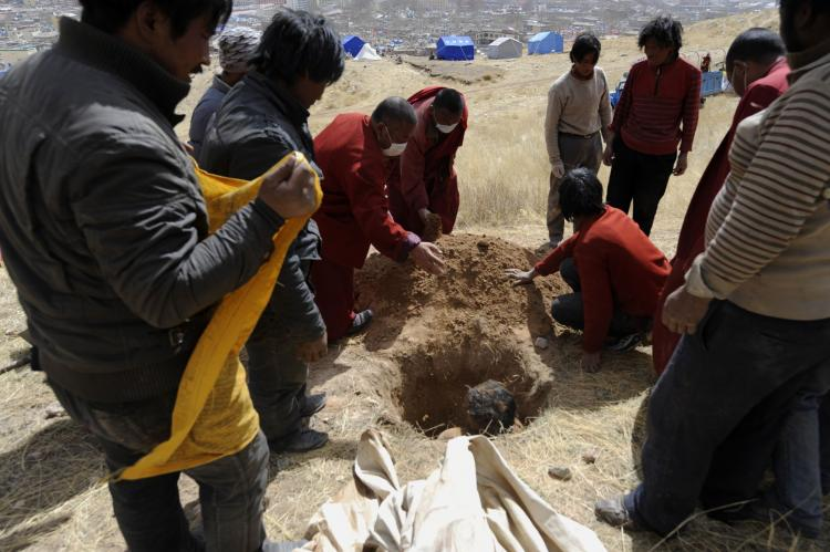 Tibetan Buddhist monks and civilians bury an earthquake victim on a hillside in Jiegu, Yushu county. ( Liu Jin/AFP/Getty Images)