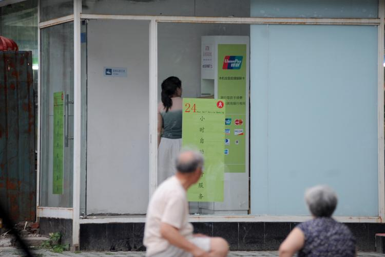 A woman tries to use a fake ATM machine near Guangamen Subway Station in Xuanwu District in Beijing on June 19. (The Epoch Times Photo Archive)