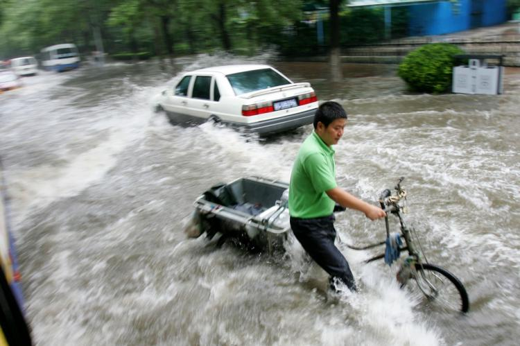 ALL WET: A man pushes a tricycle along a flooded road after heavy rain on August 10, 2008 in Beijing, China. (China Photos/Getty Images)