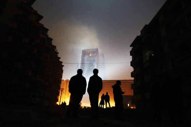 TOWER BURNS: People watch a fire at the unfinished The Mandarin Oriental hotel, that is part of complex that houses the Chinese Central Television's (CCTV) headquarters on February 9, 2008 in Beijing, China. (Feng Li/Getty Images)