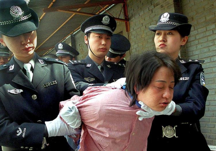 A woman prisoner is being taken away for her execution after she was sentenced to death at a sentencing rally in Beijing, China.  (AFP/Getty Images)