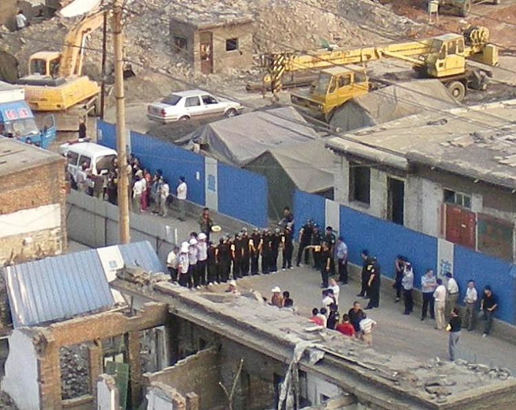 Demolition: In a typical scene in China, public security officials form a barrier to prevent residents entering an urban demolition and redevelopment site. (Blogger photo)
