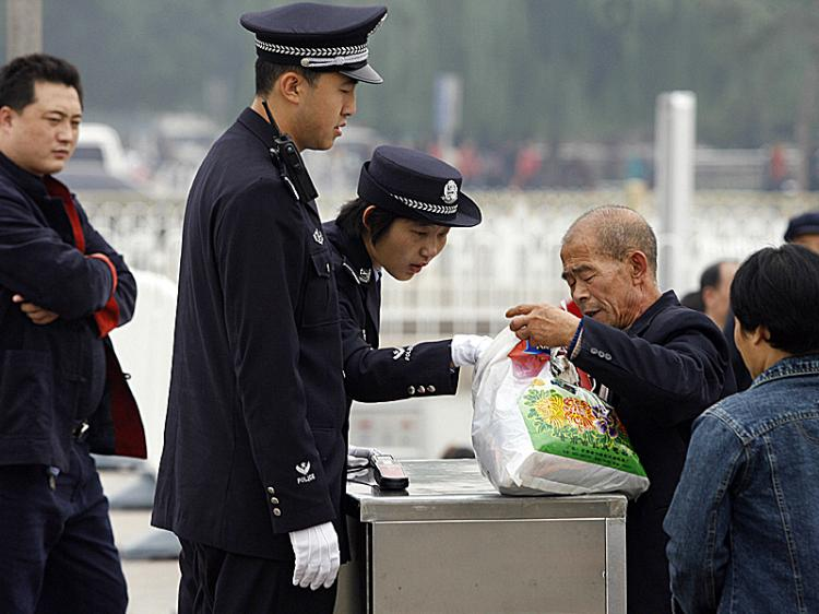 A policewoman checks a man's bag on Tiananmen Square in Beijing. Intense security measures are already in place for next month's Beijing Olympics.  (Peter Parks/Getty Images)