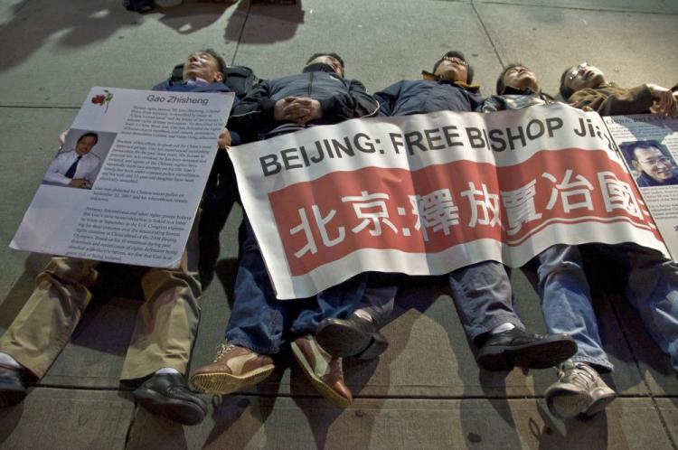 Protestors from the Democratic Forum of China lay down and drape a banner over themselves in protest of the Chinese Communist Party's 60 years of rule, at the Chinese consulate in New York, Sept. 30, 2009. (Aloysio Santos/The Epoch Times)