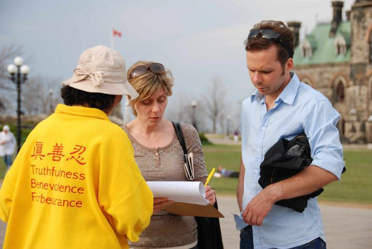Tourists on The Hill signing a petition (Samira Bouaou/Epoch Times)
