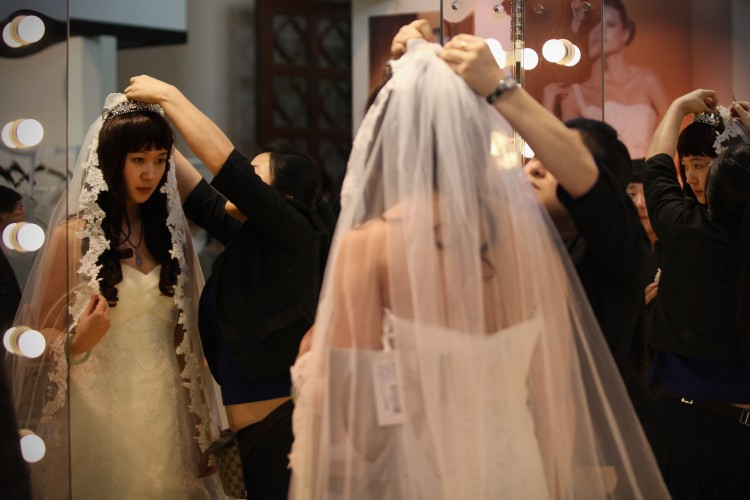 A Chinese woman tries on a wedding dress at the 2012 China Spring Wedding Expo at Beijing Exhibition Center on February 17, 2012 in Beijing (Feng Li/Getty Images)
