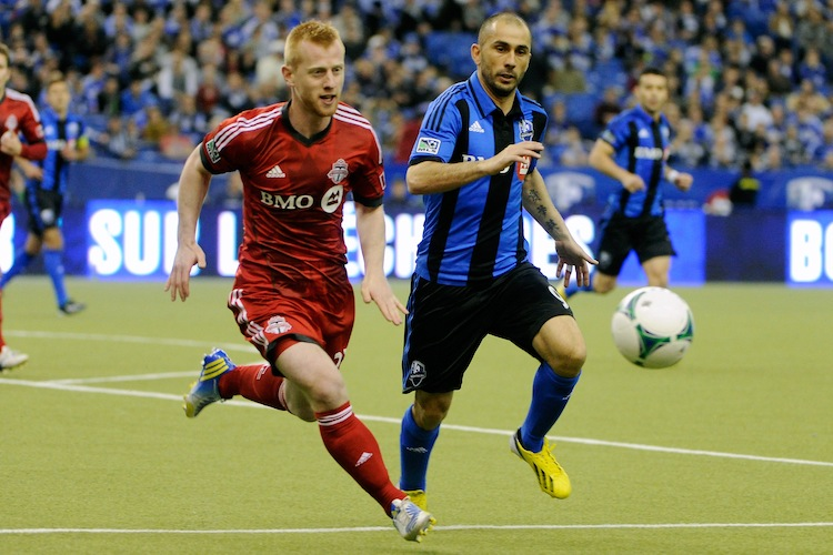 Toronto FC's Richard Eckersley (L) and Montreal Impact's Marco Di Vaio compete for the ball in MLS action at Montreal's Olympic Stadium on Mar. 16. The Impact won their home opener against their Canadian rivals. (Richard Wolowicz/Getty Images)