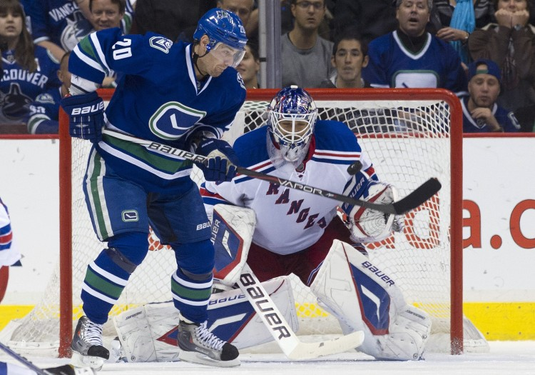 Vancouver's Chris Higgins tries to score on New York's Henrik Lundqvist in a game played on Oct. 18, 2011, in Vancouver. The Canucks and Rangers were two of the higher-spending yet more profitable NHL teams last year.  (Rich Lam/Getty Images)