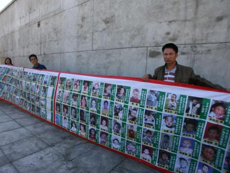Over 30 parents from various places in China holding a large banner with photos of their children in Beijing. (Epoch Times Archive)
