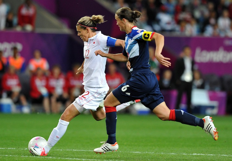 Canada's Christine Sinclair (L) gets past Great Britain's Casey Stoney in Olympic women's soccer quarterfinal action on Friday. (Paul Ellis/AFP/GettyImages)