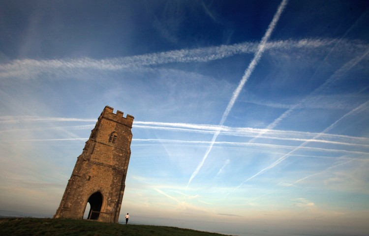 A woman looks up at the mass of contrails left by a jet aircraft crossing the sky above St. Michael's Tower near Glastonbury, England. (Photo by Matt Cardy/Getty Images)