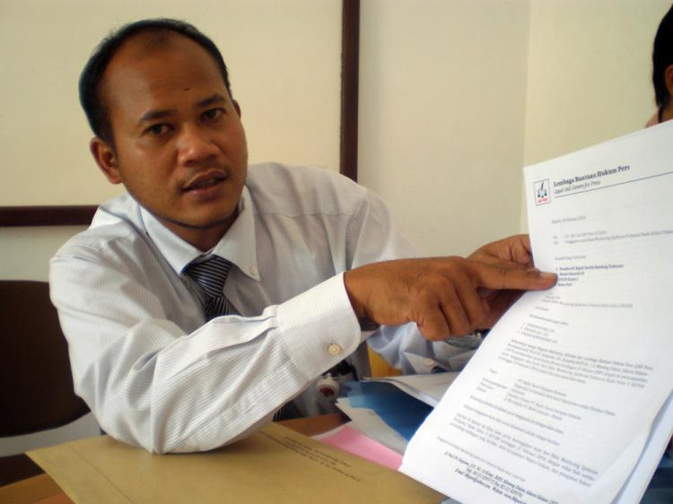 Raymond Tan holds up legal documents associated with the Radio Era Baru case. (Soleh Ali/The Epoch Times)