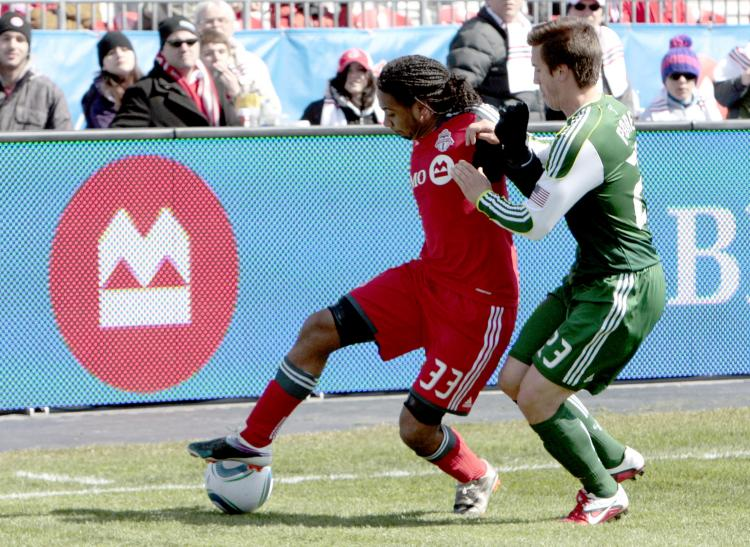 Toronto FC's Javier Martina (L) holds off Portland's Steve Purdy. (Abelimages/Getty Images)