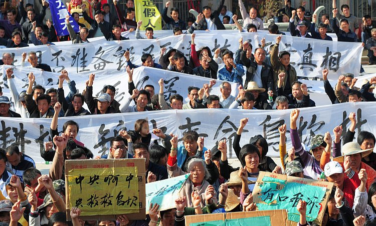 Villagers hold banners during a protest rally in Wukan
