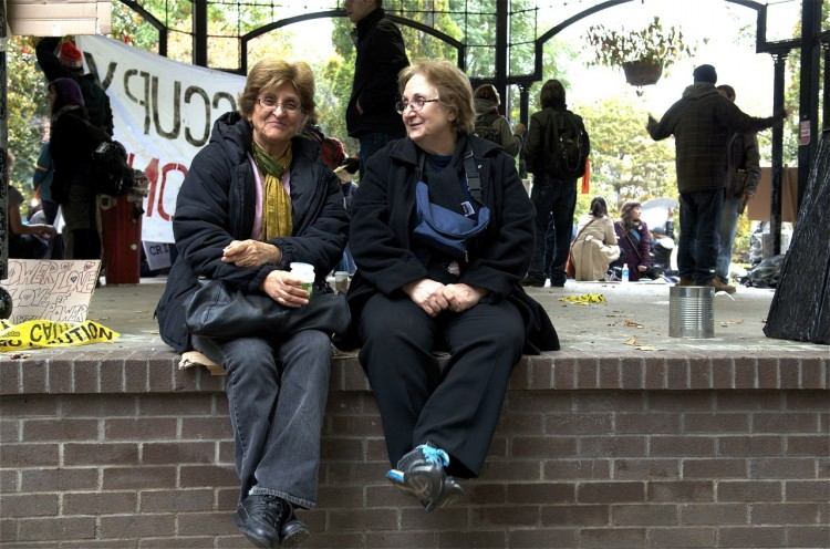 Two women sit on the gazebo at the Occupy Bay Street protest site in St. James Park, Toronto.  (Matthew Little/The Epoch Times)