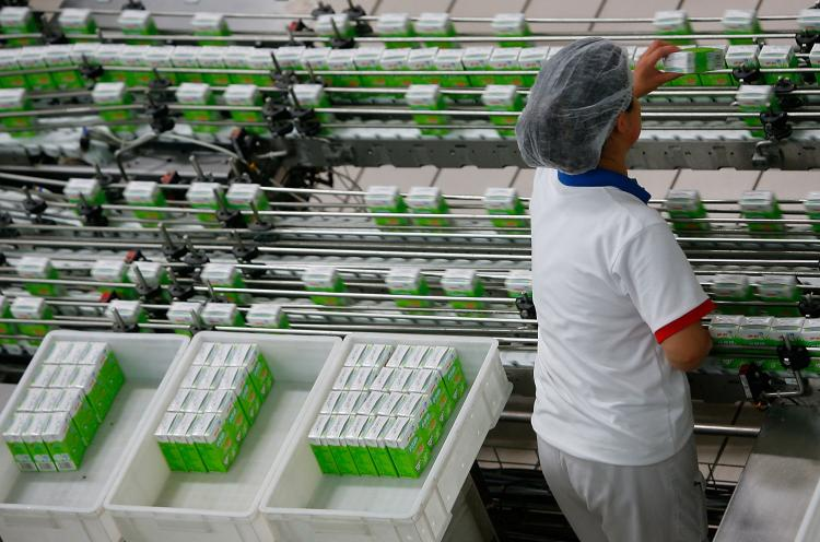OLYMPIC SUPPLIER: A worker labors on a liquid milk product line at a Yili Industrial Group Company plant. Melamine was found in Yili Group dairy products, which raises the question of whether these products were supplied to the Olympics. (China Photos/Getty Images)