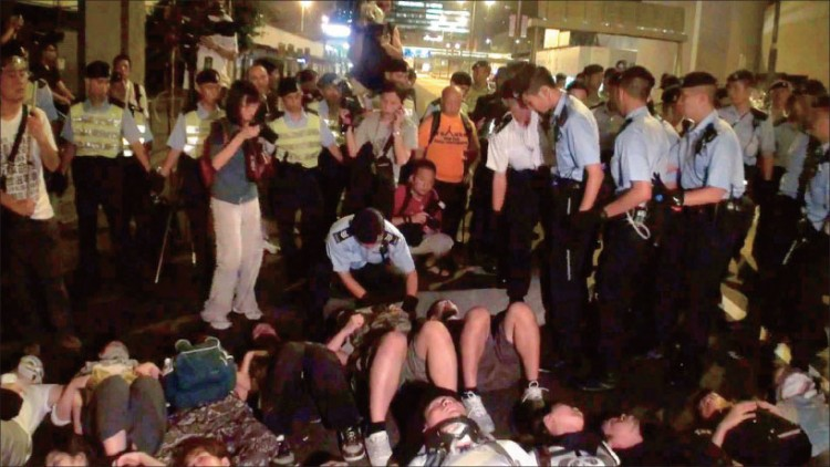 Ms. Cai Wenwen (dressed in dark blouse and white pants and holding a camera), an intern reporter from NTDTV, was arrested by police while photographing a protest in Hong Kong on the night of July 1.  (Internet Image)