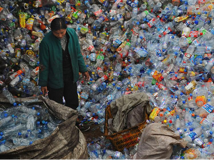 A woman stands amongst a huge pile of used plastic bottles at a plastics recycling mill which is ceasing production as the global financial crisis starts to bite in China's recycling industry on October 29, 2008 in Wuhan of Hubei Province, China. (China Photos/Getty Images)