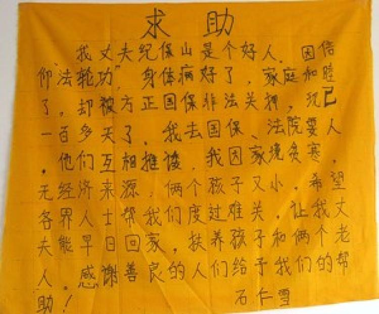 A woman from Fangzheng County writes her appeal on a piece of yellow cloth as she begs for food with her infant after her family was torn apart by persecution. (The Epoch Times)