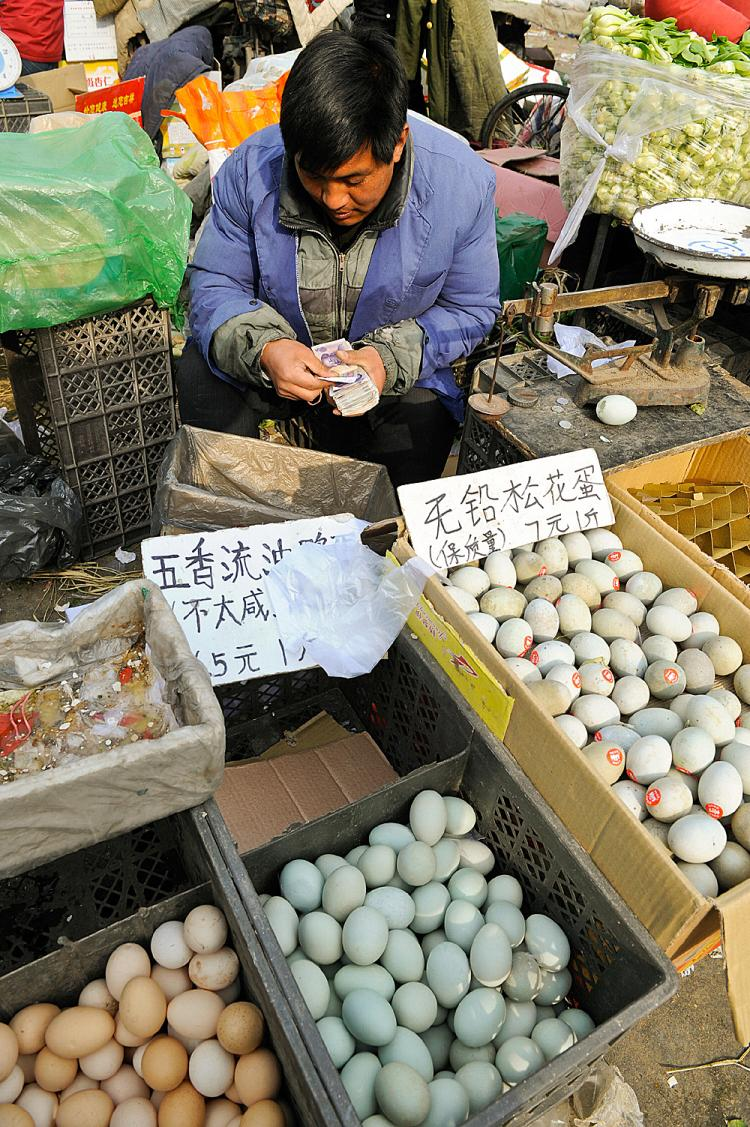 An Chinese eggs vendor counts Chinese yuan notes at a market in Beijing.  (Teh Eng Koon/AFP/Getty Images)