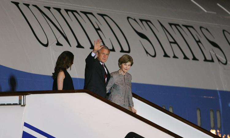 U.S. President George W. Bush (C) waves as First Lady Laura Bush (R) and daughter Barbara Bush walk down the steps from Air Force One after arriving August 7, 2008 in Beijing, China. Chinese authorities are anxious to publicize a list of about 80 foreign  (Andrew Wong/Getty Images)
