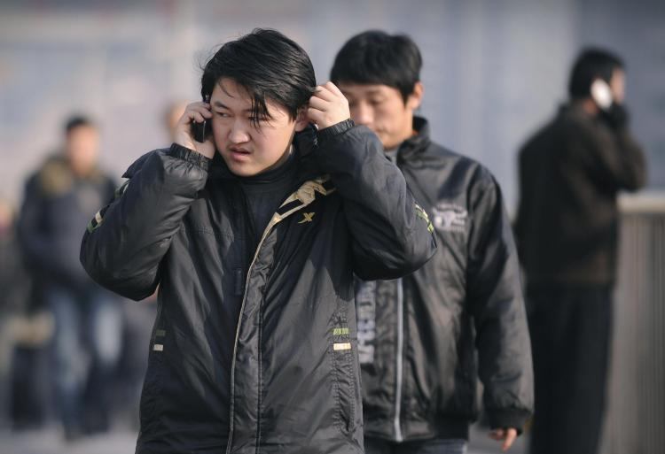 Cell phone virus affects a million: People use mobile phones on a street in Beijing on January 7, 2009. (Peter Parks/AFP/Getty Images)