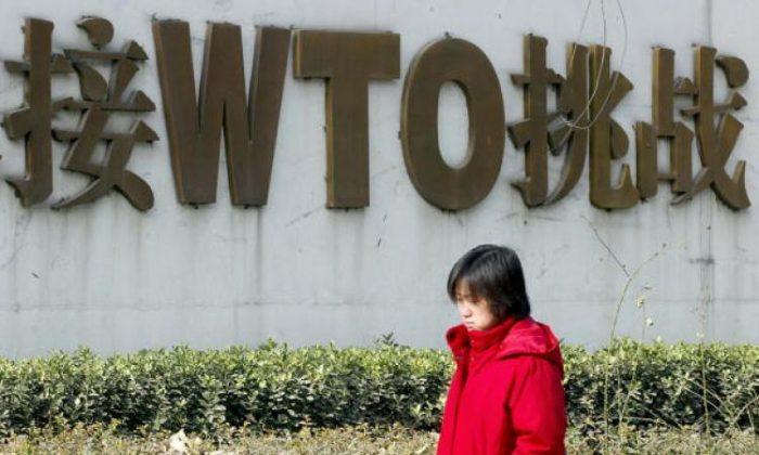 A Chinese woman walks pass a billboard boasting China's World Trade Organization (WTO) membership. The U.S. is nurturing a $73 billion trade deficit in technology products with China. (Goh Chai Hin/AFP/Getty Images)