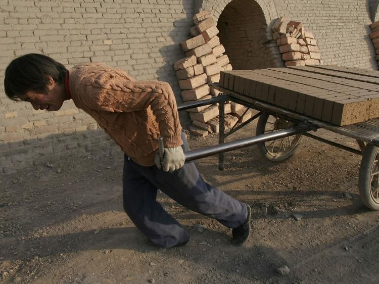 A worker removes half-made bricks at a brick factory in Huangzhong County of Qinghai Province, China. (China Photos/Getty Images)