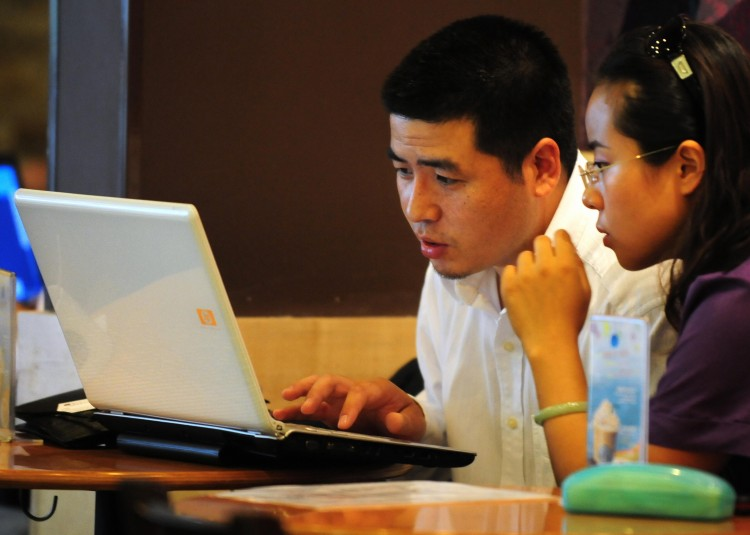 Chinese netizens use a laptop computer at a wireless cafe in Beijing in 2009. China's largest microblog Sina Weibo plans to implement more stringent Internet controls to stamp out 'rumors.' (Frederic J. Brown/AFP/Getty Images)