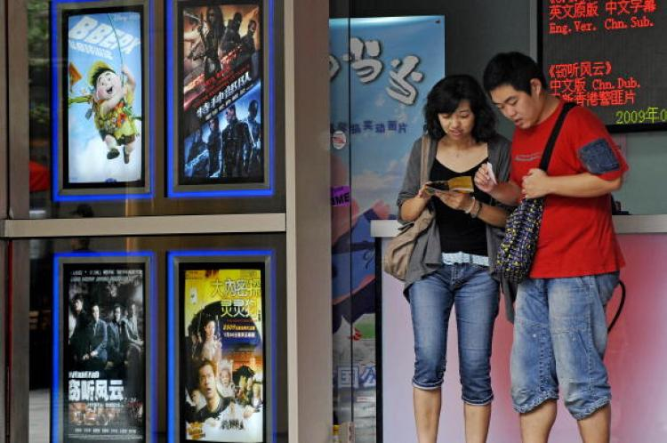 A man and a woman check their movie tickets in Shanghai. Movie ticket prices have skyrocketed in China, and now a ticket costs as much as 5 percent of per capita monthly income. (Philippe Lopez/AFP/Getty Images)