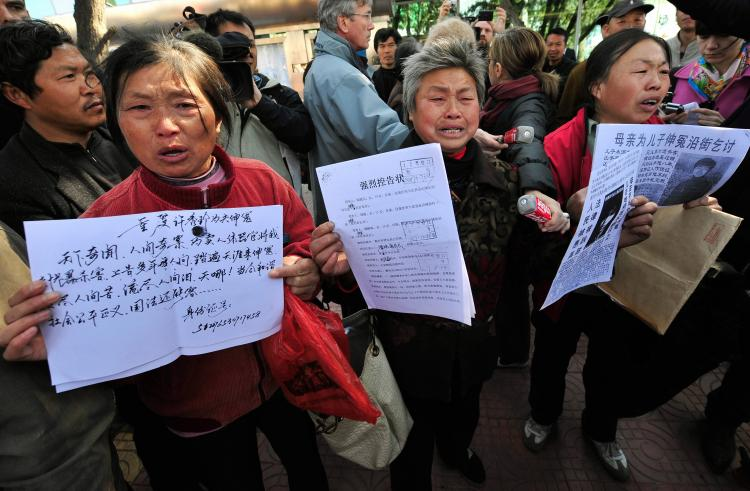 Agitated Chinese petitioners show documents during a gathering outside a courthouse while human rights activist Hu Jia was in attendance inside the court, in Beijing on April 3, 2008. The petitioner's activities were unrelated to the sentencing. (Teh Eng Koon/AFP/Getty Images)