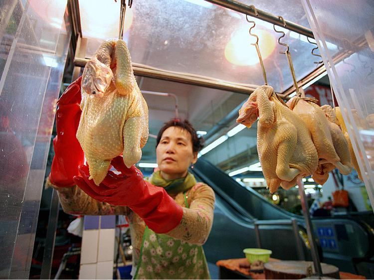 A poultry vendor weights sells cooked chickens at a market in Hong Kong. (Samantha Sin/AFP/Getty Images)