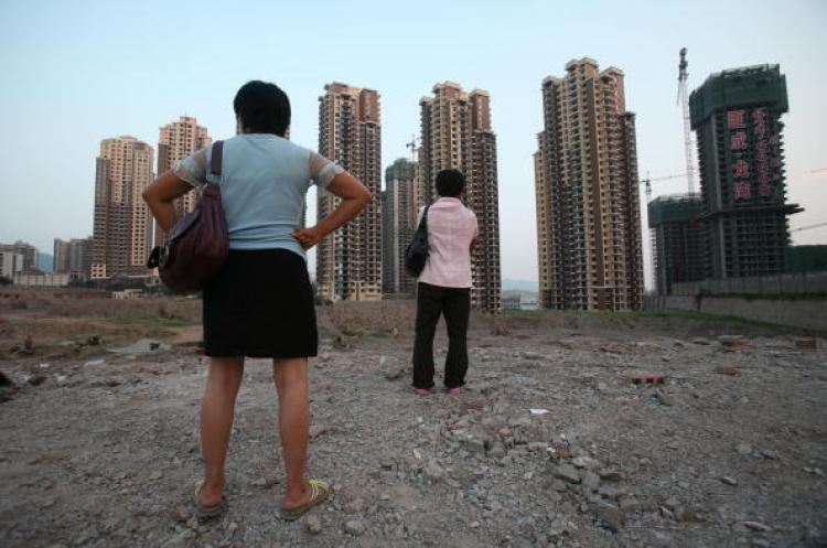The Chinese real estate market is about to have a new tax added. Pictured, two women in Chongqing are looking at apartment buildings under construction. (AFP/Getty Images)