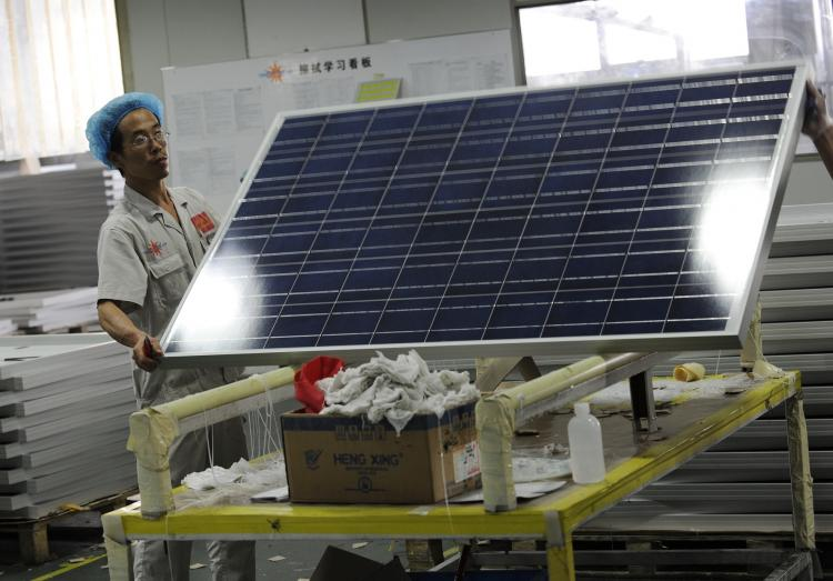 China's clean energy policies are being investigated by US trade officials. Above, a worker lifts a solar panel in the Yingli Solar factory, in Baoding, Hebei province, China in September. (PETER PARKS/AFP/Getty Images)