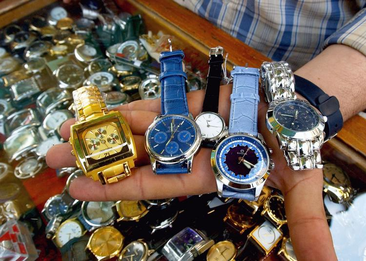 A watch-seller shows his fake watches including Rolexes for about $15 or $20.  (Wathiq Khuzaie/Getty Images)