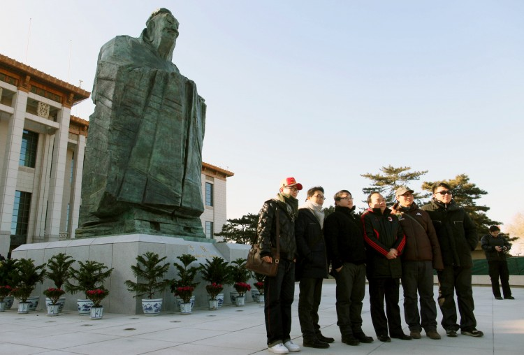 NOW YOU SEE HIM: Chinese tourists pose in front of Confucius outside the National Museum at Tiananmen Square in January. The statue was removed without explanation four months later, highlighting the Communist Party's ambiguity in executing its new brand of Confucius propaganda. (STR/AFP/Getty Images)