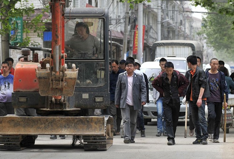 Chinese authorities carry sticks as they prepare to stand guard before workers demolish houses which are claimed illegal by local government in Wuhan, central China's Hubei Province on May 7, 2010. Land seizures have been a problem for years in China and forced evictions have not been uncommon. (AFP/Getty Images)
