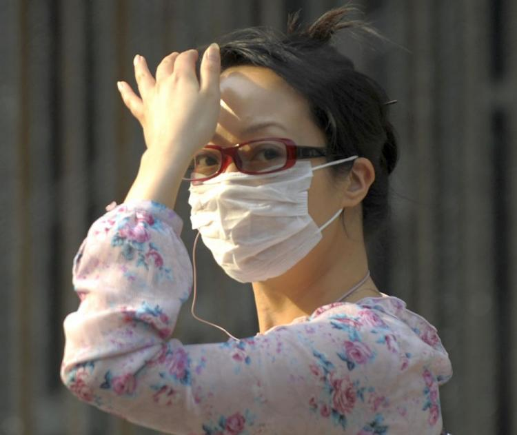 A woman wearing a face mask walks along a street in Beijing on May 5, 2009. Influenza H1N1 is spreading rapidly throughout all 31 provinces in mainland China. (Liu Jin/AFP/Getty Images)