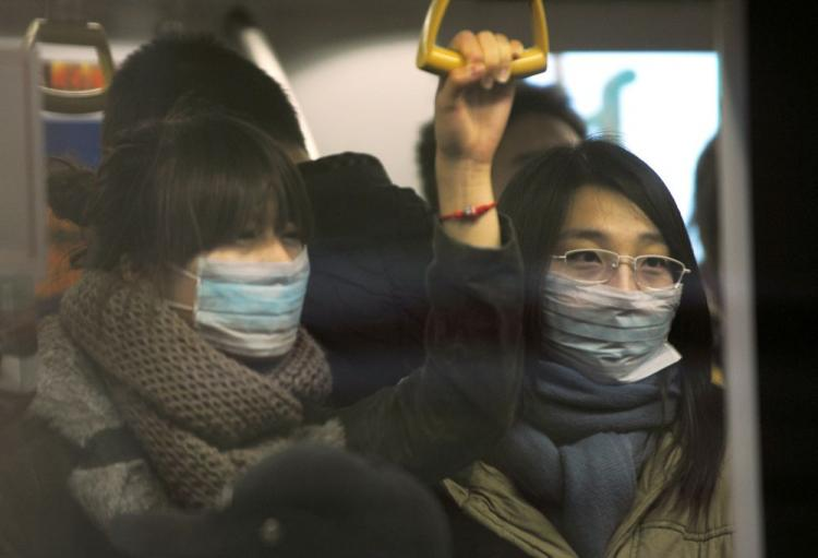 Two women wear masks while riding on the Beijing subway on December 2, 2009. Serum or plasma from people who have recovered from the H1N1 virus is being used to treat patients in China who are in a serious condition with the virus. (Peter Parks/AFP/Getty Images)