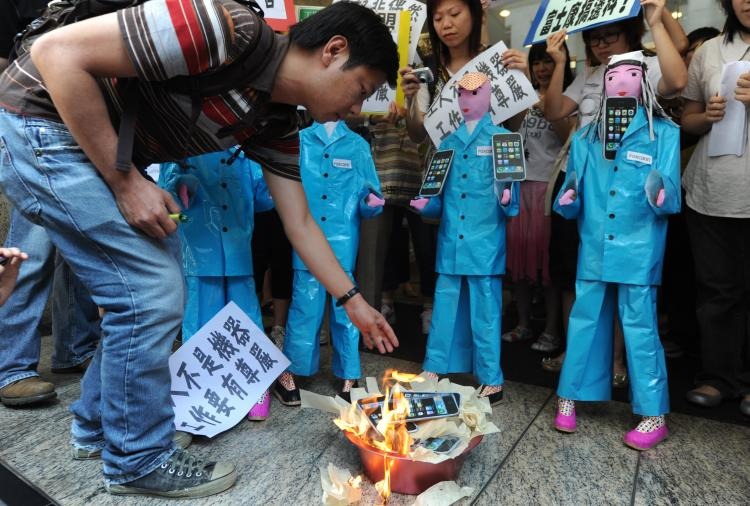 Protestors from SACOM (Students and Scholars Against Corporate Misbehavior) burn effigies of Apple iPhones near the offices of Foxconn in Hong Kong on May 25. The founder of Foxconn Group on Monday broke his silence over a string of suicides by its employees.  (Mike Clarke/Getty Images)