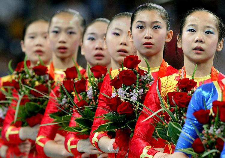 The girls of the gold-medal-winning Chinese women's gymnastics team might have seen their parents once a year since age three, when the state put the girls in a training program. (Al Bello/Getty Images)