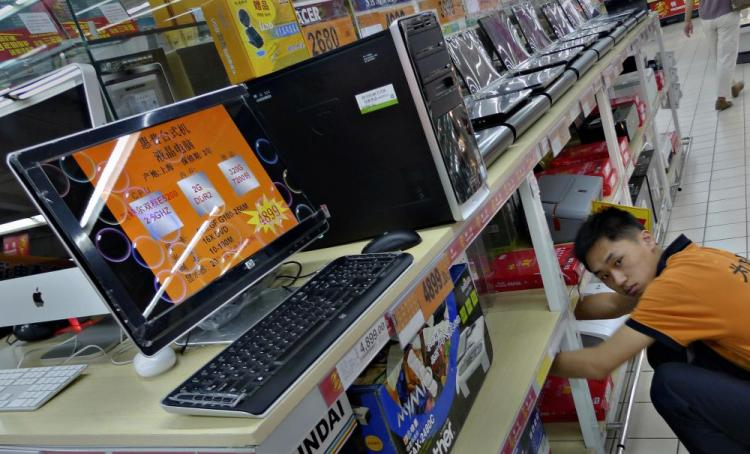 A salesman adjusts computer items at a supermarket in Beijing. The Chinese regime's Green Dam-Youth Escort filtering software has become a censorship boondoggle. (Liu Jin/AFP/Getty Images)